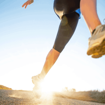 female runners legs on a run with sunlight on a dirt road