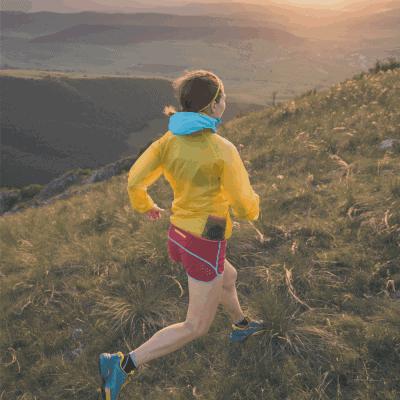 female runner long distance mountain side at sunrise
