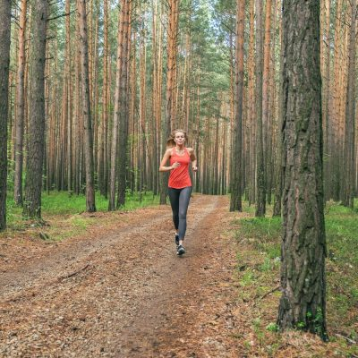 female runner in woods doing a recovery run