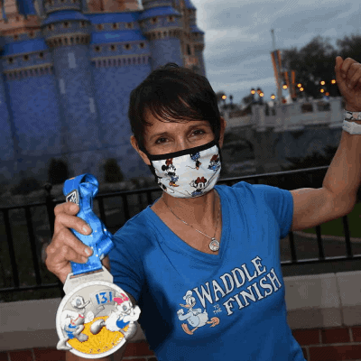 female runner disney castle with rundisney medal