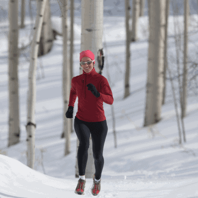 female running in snow in forest