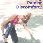 female runner with pain in her ankle kneeling on ground