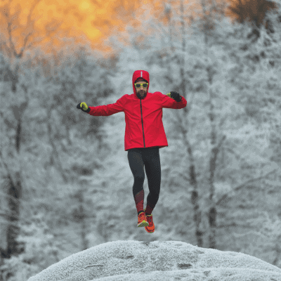 Man on top of hill running in snow and forest